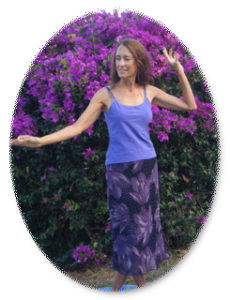 Deva doing Tantra Goddess Kundalini dance near purple flowers on Maui