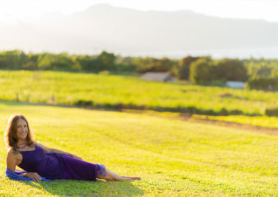 Maui Tantra Coach Deva Dasi reclining outside on pasture grass