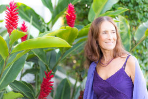 Intimacy Coach Deva Dasi with red ginger plants on Maui